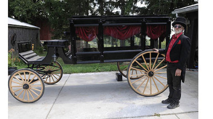 Bill Wolfe stands in front of a carriage used primarily for funerals at his horse-drawn carriage business, which supplies carriages for everything from funerals to weddings. There are more than 20 different carriages and more than 20 horses at his farm in Apollo.