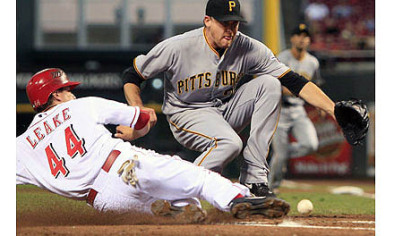 The Reds&#039; Mike Leake scores as Pirates starting pitcher Kevin Correia reaches for the ball after Correia threw a wild pitch in the second inning.