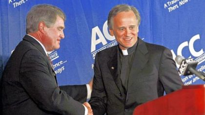 Notre Dame president Rev. John I. Jenkins, right, is congratulated by Atlantic Coast Conference commissioner John Swofford at a news conference in Chapel Hill, N.C., where it was announced that the Irish would join the ACC beginning in 2015.