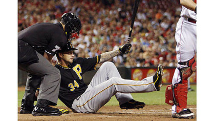 The Pirates&#039; A.J. Burnett, center, falls to the ground after striking out with the bases loaded in the fourth inning. Home plate umpire Manny Gonzalez helps out at left.