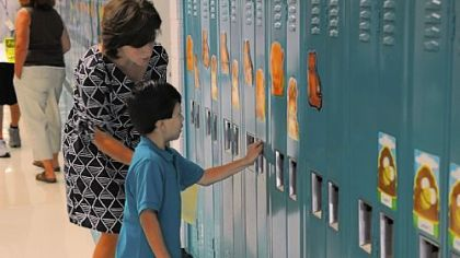 Gateway kindergarten teacher Jill Mutschler helps 5-year-old Jesus Ramos with his locker during Cleveland Steward Elementary's two-day kindergarten orientation in August. Full-day kindergarten is now available districtwide.