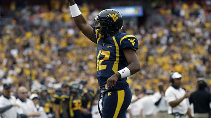West Virginia quarterback Geno Smith reacts after a touchdown during the first half of an NCAA college football game against James Madison.