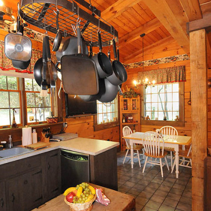 A rustic, natural-finish butcher block island is topped by a hearty pot rack filled with pots in every size and shape -- both decorative and functional.