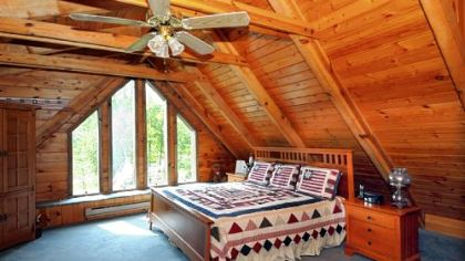 The 20-by-18-foot master bedroom has a bank of floor-to-ceiling windows accentuating the roof peak.