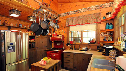 The 21-by-13-foot kitchen has mostly open wood shelving at various heights, leaving space for canisters and decorative items.