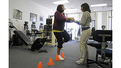 Nettie Gibson, left, who was seriously injured by a drunken driver in August 2011, does an exercise with the help of therapist Annie Ursom at East Suburban Sports Medicine in Monroeville.