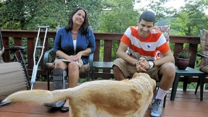 Nettie Gibson sits on her porch with her son, Dominic, 13, and their dog, Dude.
