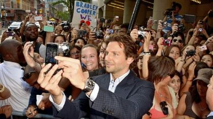 Bradley Cooper poses for a photo with fans at the Toronto International Film Festival. The actor had two films screening there.