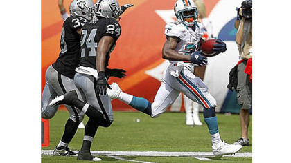 The Dolphins' Reggie Bush runs for one of his two TDs Sunday.