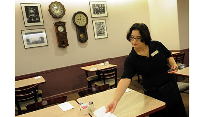 Nicole Kelsey, of Mt. Oliver, sets tables in preparation for Tuesday's re-opening of the Tic Toc Restaurant in Macy's.