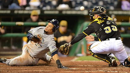 The Brewers' Carlos Gomez slides past the tag of Pirates catcher Michael McKenry.