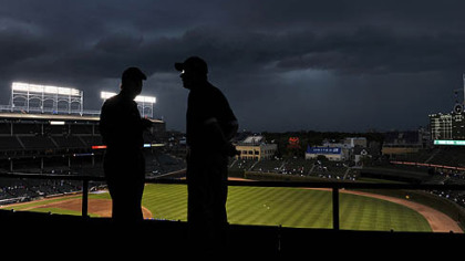 Storm clouds move over Wrigley Field as ushers look at the empty stands during a delay to the start of the game between the Pirates and Cubs tonight in Chicago.