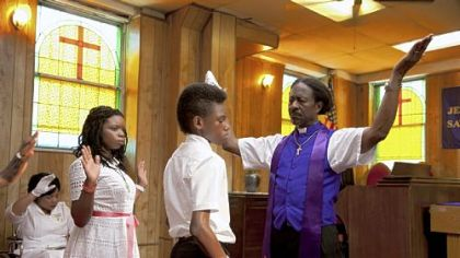 "Kimberly Hebert-Gregory as Sister Sweet (seated, background), Toni Lysaith as Chazz Morningstar, Jules Brown as Flik Royale and Clarke Peters as Bishop Enoch Rouse in Spike Lee's ""Red Hook Summer."""