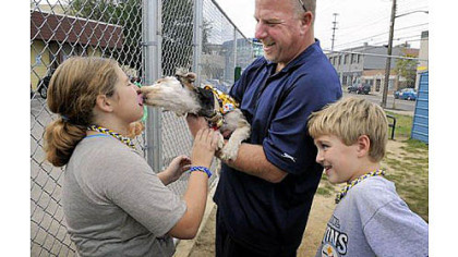 new member of the family Oscar, a puppy found last month in a garbage can in Garfield, plants a wet one on Ryleigh Long, 10, at the Animal Rescue League Shelter & Wildlife Center in East Liberty on Friday. The Long family of West Deer ? including Dave, center, Noah, right, and Wendy, not pictured ? have adopted the mutt.