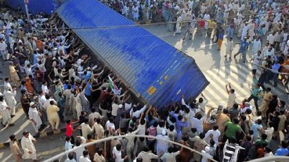 Pakistani Muslim demonstrators topple a freight container, placed by police in Lahore as a roadblock during a protest against an anti-Islam film.