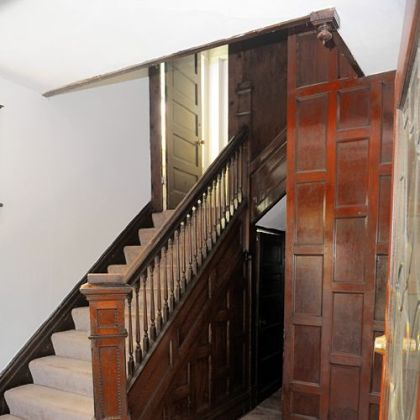 The entry features wood paneling and a staircase that has the original wood finish.