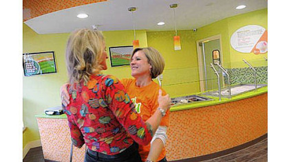 Ellie Hall, right, embraces Lynne Jones of Colorado as they prepare to open Yogli Mogli yogurt shop on Washington Road in Mt. Lebanon Saturday. Ms. Hall is the widow of the late Brian Hall, co-owner of the business, who died recently in a small plane crash. Ms. Jones is the wife of the other co-owner.