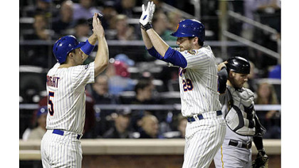 The Mets' David Wright, left, greets Ike Davis at the plate as Pirates catcher Michael McKenry adjusts his helmet after Wright scored on an Ike Davis two-run home run in the fourth inning.
