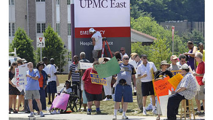 Protesters demonstrate in front of the new UPMC East facility in Monroeville in July, as workers put the finishing touches on the sign.