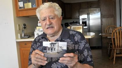 "James Roberto, 88, holds a photo of the ""little white house"" he lived in on Marion Street in Uptown for more than 40 years before he sold it to UPMC Mercy. Mr. Roberto, who had rejected several offers from Mercy Hospital, sold the property to UPMC for $573,847."