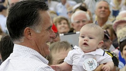"Mitt Romney picks up a baby wearing a ""Dump Obama"" pin as he campaigns in Pueblo, Colo."