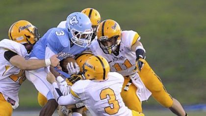 Central Valley's Jordan Whitehead, being gang-tackled by Montour defenders, leads the Warriors rushing attack.