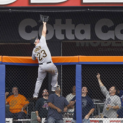 Pittsburgh Pirates right fielder Travis Snider climbs the fence to rob New York Mets' Mike Baxter of a home run during the second inning.