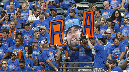 Fans pay tribute to New York Mets pitcher R.A Dickey, who is going for his 20th victory, during a baseball game against the Pittsburgh Pirates at Citi Field in New York.