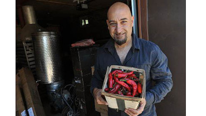 Nick DiCio of Reyna Foods displays a basket of chiles grown locally from Hatch seed.