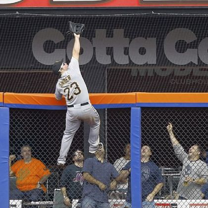 Travis Snider climbs the fence to rob the Mets' Mike Baxter of a home run Thursday at Citi Field in New York.