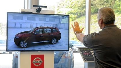 Gary Carr, general manager of Pittsburgh East Nissan, demonstrates the Pathfinder Kinect Experience in the showroom.