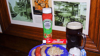 Wurst plate includes (left to right): Nurnberger bratwurst, knackwurst, bratwurst, sauerkraut and rottkraut. In background is curry ketchup, extra spicy mustard and Iron City Amber beer. Photos in frame are of Carl Meyer&#039;s Hof in Buffalo, N.Y.