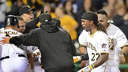 Pirates outfielder Andrew McCutchen is greeted at home after hitting a walk-off homer against the Reds in the ninth inning Saturday night at PNC Park.