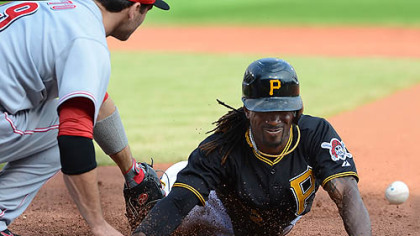 Pirates center fielder Andrew McCutchen dives back to first and heads to second on an overthrow by the Reds.