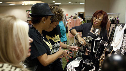 Attendees gather around the Traci Lynn Jewelry booth at the Fashion Ave Vendors Fair at the Clarion Hotel & Convention Center in Green Tree.