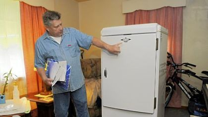 Richard Linnert shows off Pennsylvania's oldest refrigerator at his Baldwin Borough home. Mr. Linnert decided to recycle the appliance, which once belonged to his aunt, through Duquesne Light's Watt Choices program.