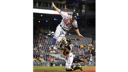 Pirates catcher Michael McKenry tags out high-flying Braves outfielder Reed Johnson at home plate Tuesday at PNC Park.
