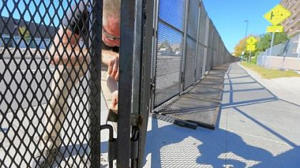 Mark Stahlbaum works on Tuesday on the security perimeter fence in preparation for tonight's first presidential debate at the University of Denver.