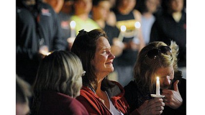 Denise McNerney, mother of slain Washington & Jefferson football player Tim McNerney, holds a candle at a vigil in front of members of the football team.