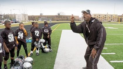 "A coach gives a pep talk to some young football players in a scene from Steve James' ""Head Games."""