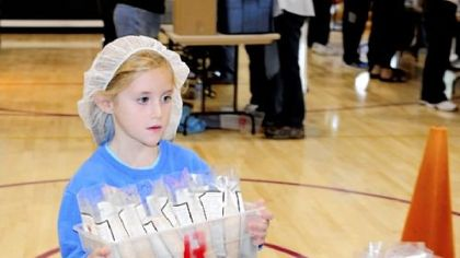 Kendall Smith helps pack meals Saturday at Christ United Methodist Church in Bethel Park. Kendall's role was to carry items across the gym.