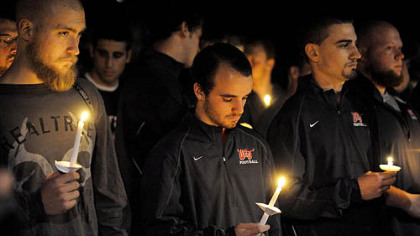 Washington & Jefferson College football players hold candles Thursday night in a vigil for their slain teammate.
