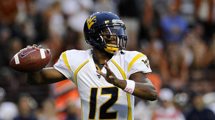 West Virginia quarterback Geno Smith looks for a receiver during the first quarter.