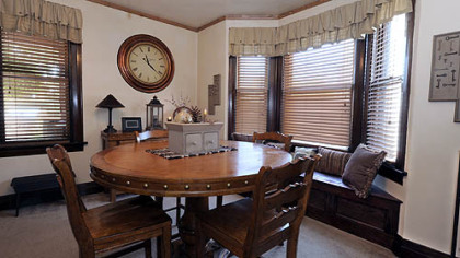 The dining room has a gas fireplace with a large carved oak mantelpiece and mosaic ceramic tile surround.