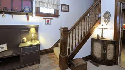 The entryway features the original woodwork on the staircase, windows, baseboards and door frames.