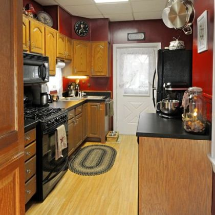 The kitchen has oak cabinets, solid-surface countertops and a wood laminate floor.