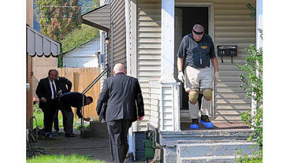 Westmoreland County detectives investigate at a house on Third Avenue in Arnold on Friday. Police said a mother and her grown son were slain in the home.