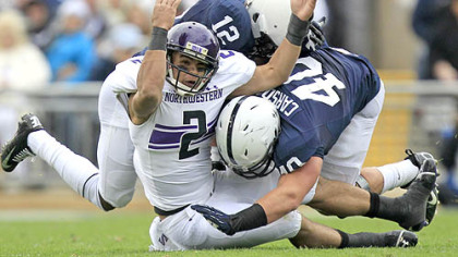 Northwestern quarterback Kain Colter is tackled by Penn State cornerback Stephon Morris and linebacker Glenn Carson (40) as he attempts to catch a pass during the second quarter of today's game in State College.
