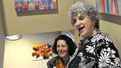 Artist Zivi Aviraz and Lila Hirsch Brody, right, who has taught painting classes at the Jewish Community Center for many years, show off some of Ms. Aviraz's paintings in Jason Kramer Hall, which is home to 10 adults with intellectual disabilities in Squirrel Hill.
