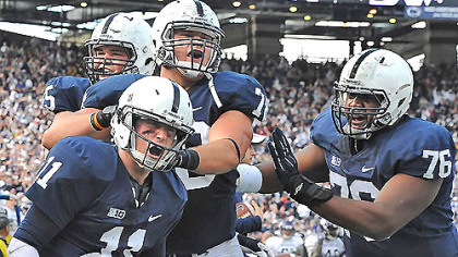 Penn State quarterback Matt McGloin, left, is congratulated by teammates after he scored the game-winning touchdown against Northwestern Saturday  afternoon at Beaver Stadium in State College.